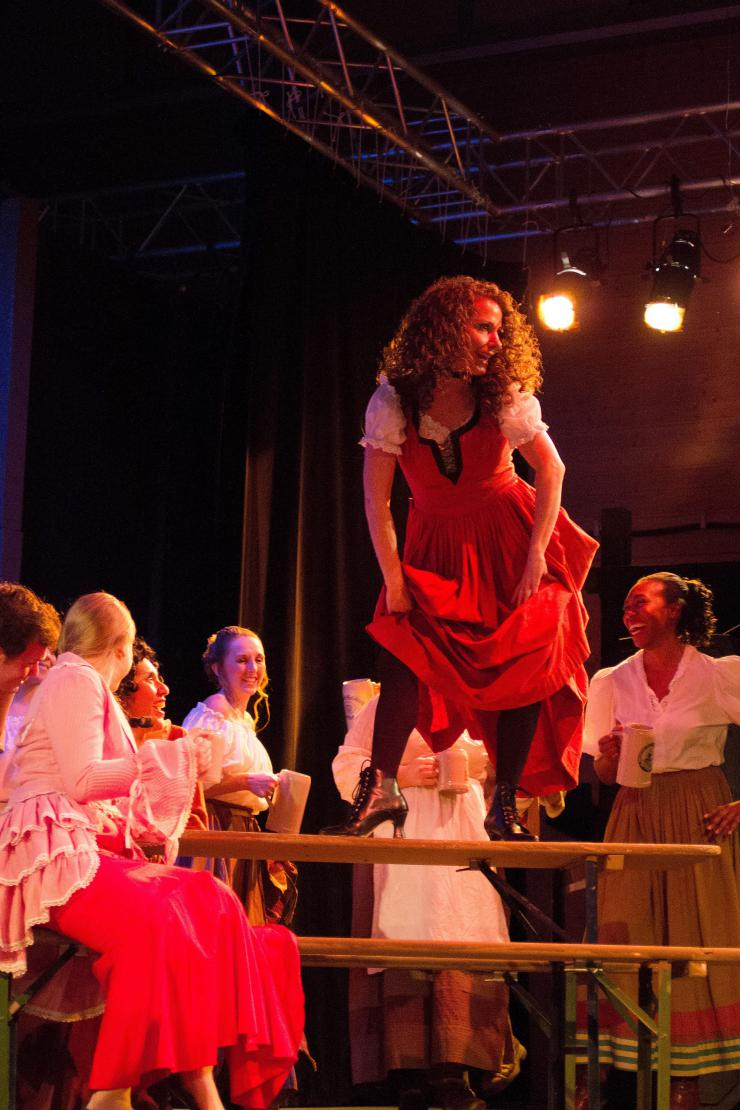 actress dances on table, surrounded by chorus of actresses