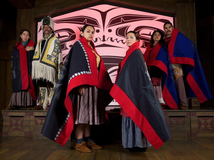 six performers onstage wearing traditional Tlingit garments