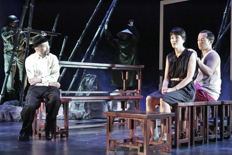 Three actors sitting on stage