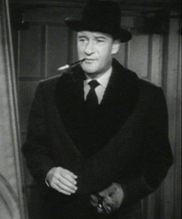 a man with a coat and cigarette