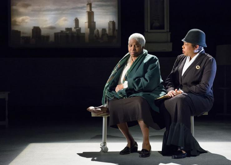 Two women on a bench on stage
