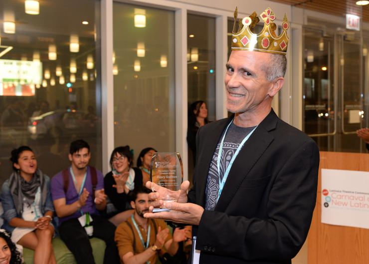 Man holding a reward while wearing a plastic crown