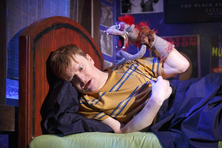 Actor on bed with a hand puppet