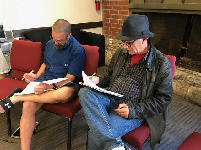 Two men sit and look at scripts