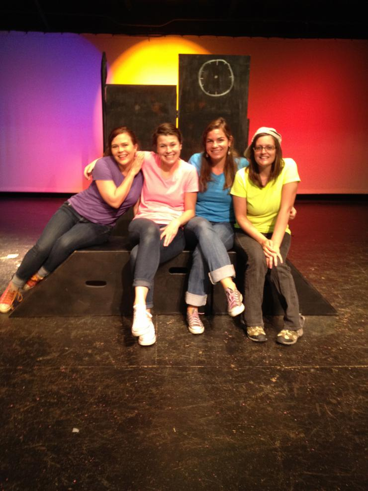 Four women in bright shirts on stage