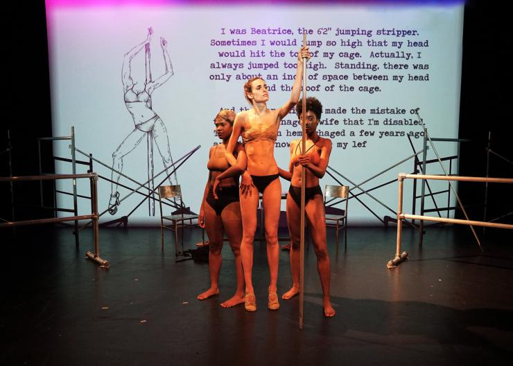three performers pose onstage by a pole with projected text behind them