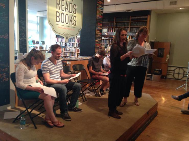 Actors on a small stage doing a reading