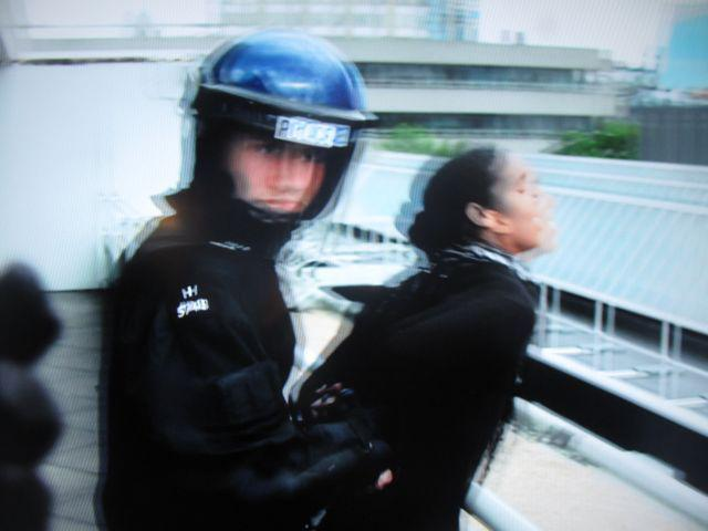 A cop in riot gear handcuffing a woman