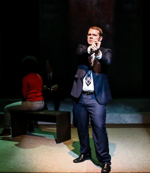 Actor stands menacingly onstage with hands pointed like a gun