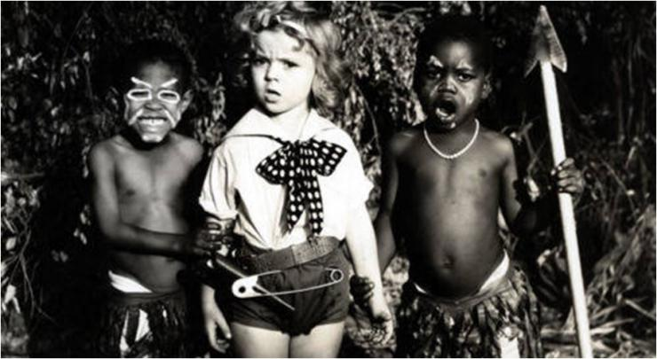 a white child with two black children wearing face paint