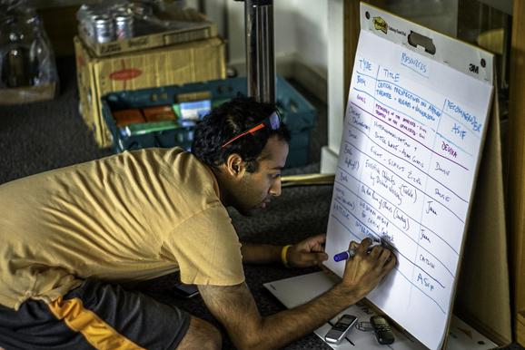 man writes on large piece of paper