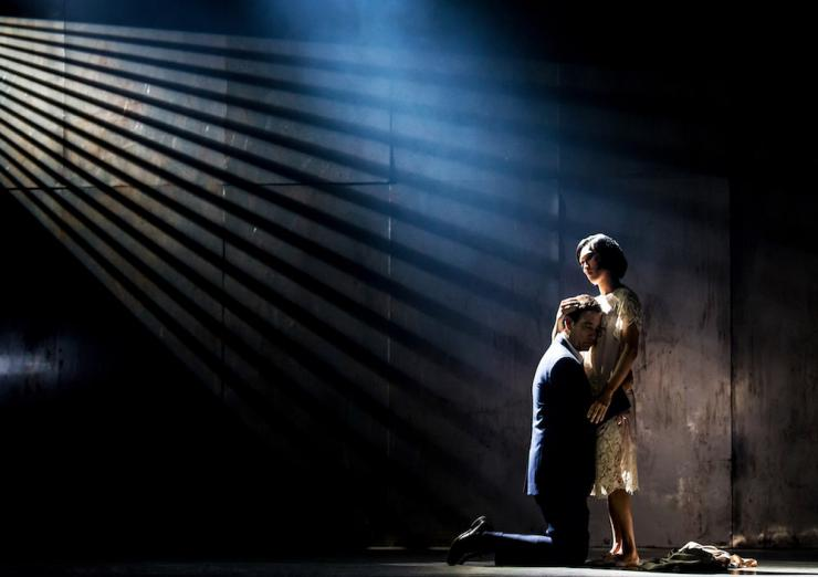 two performers embrace on a dimly lit stage