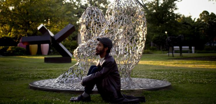 Actor sitting in a sculpture garden