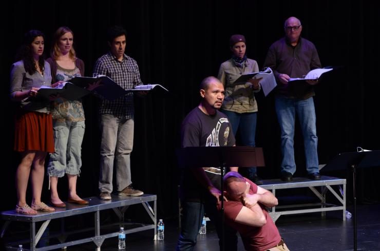 Seven actors in a reading, one actor on their knees