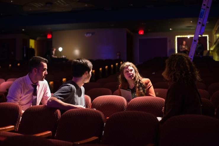 four people sitting in theatre chairs