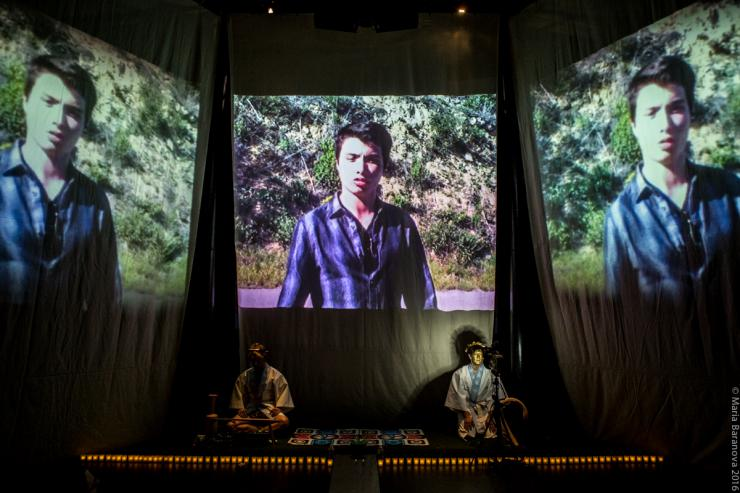 Two actor sit on stage under the projected videos of a man
