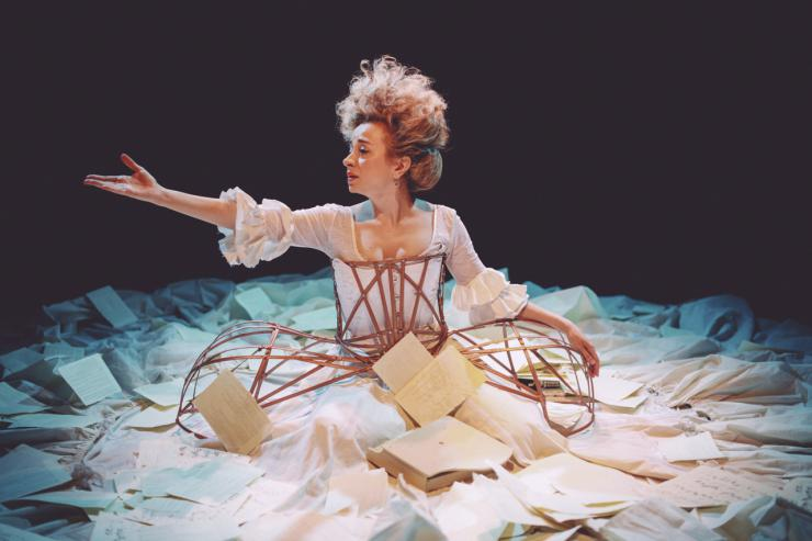 Actor in circular arrangement of papers reaching out