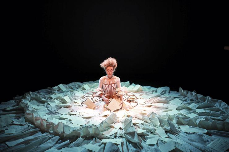 Actor in the center of a circular arrangement of papers