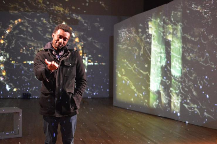 Man looking at his hand in front of projections of stars