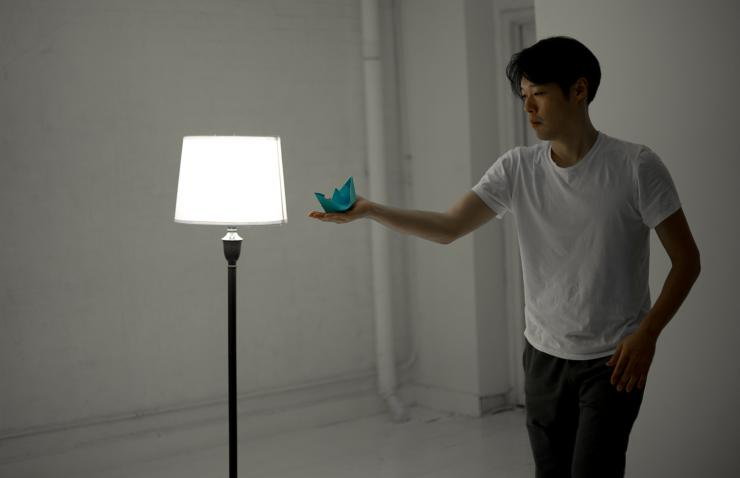 A man holds a blue boat toward a lamp