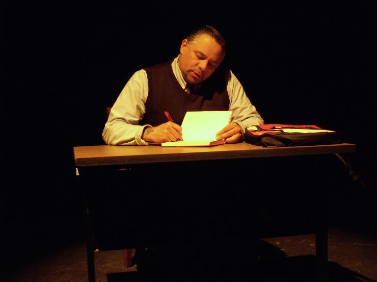 a man writing on stage