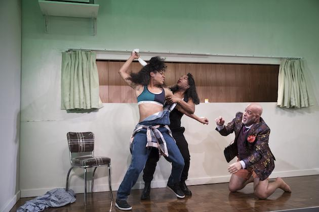 three performers fighting onstage