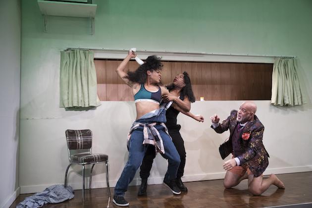 three performers fighting onstage