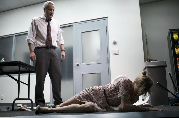 a woman on a floor and a man looking at her