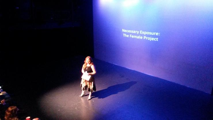 "Woman on stage in front of a projection that reads: ""Necessary Exposure: the Female Project."""