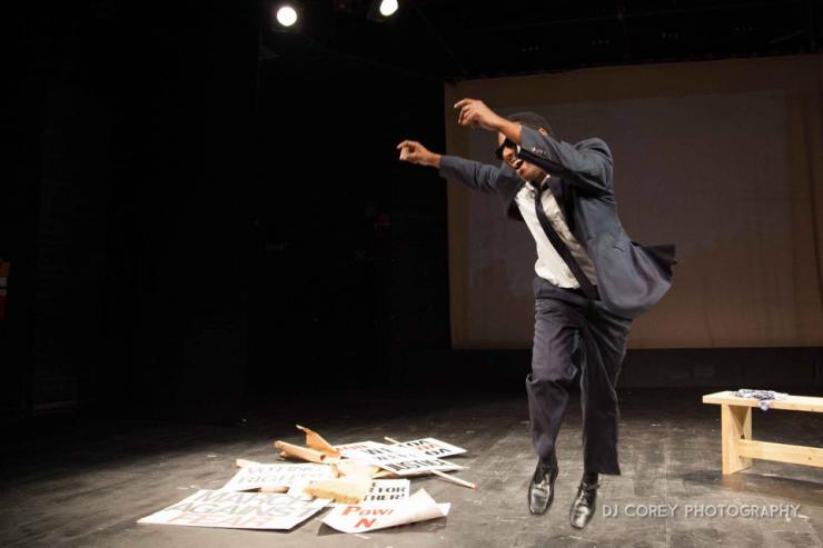 Actor dancing on stage around discarded protest signs