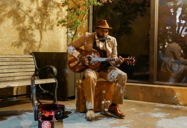 man playing guitar and harmonica