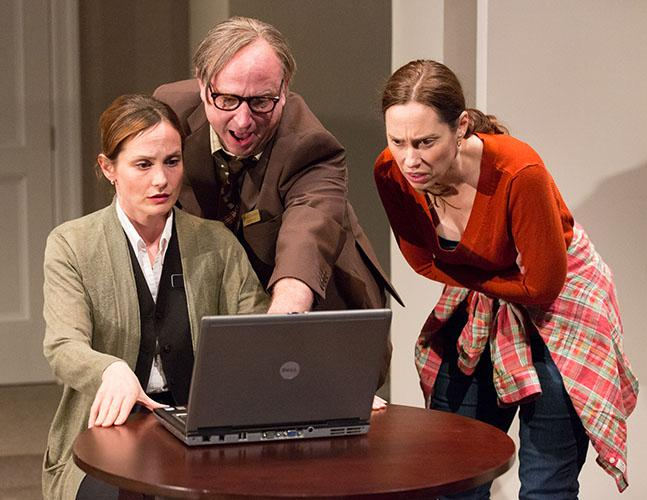 Three people looking at a computer on stage