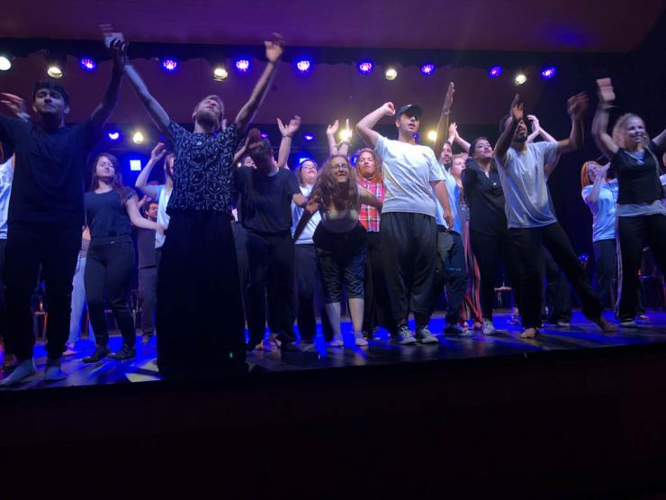 large group of performers take their curtain call