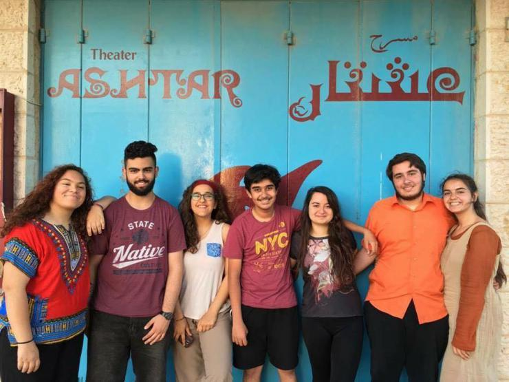 seven youth smile in front of Ashtar Theater