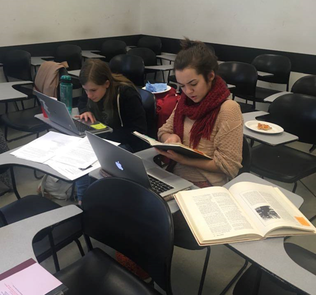 Two students sit at desks, consulting books and computers