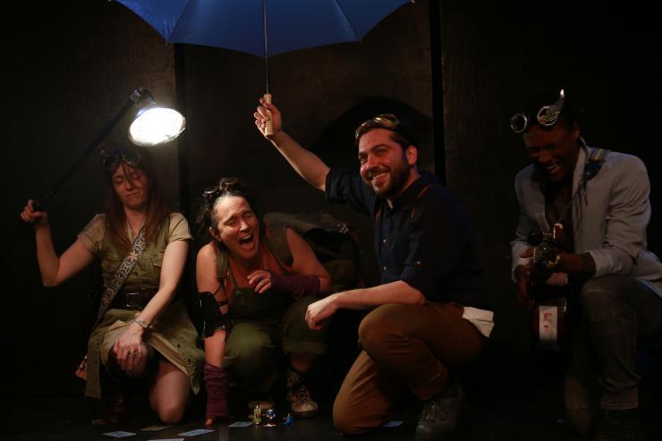 four actors smiling in costume