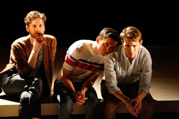 three actors sit onstage