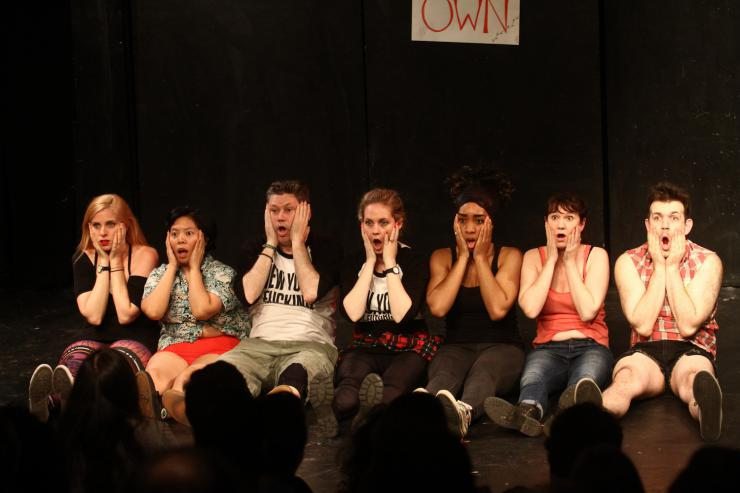 seven actors sit in a line, making a face