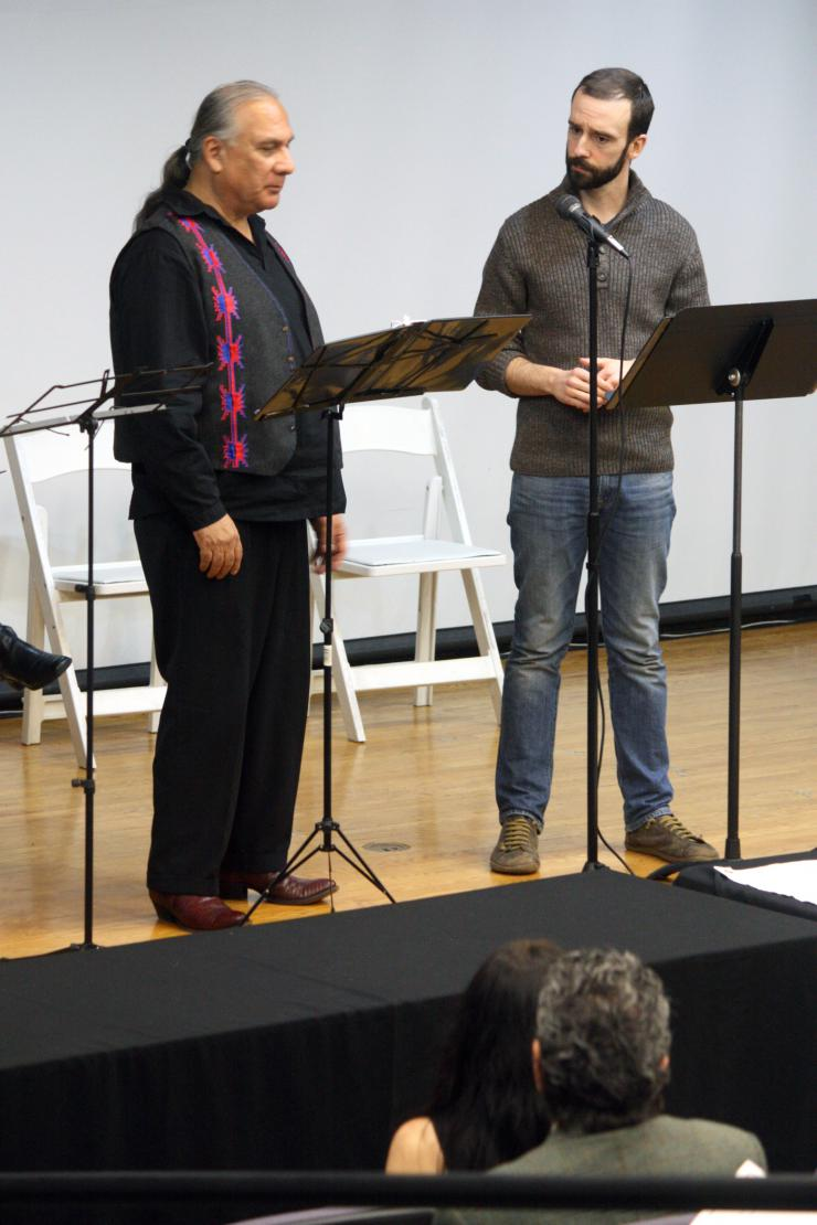 Two performers reading on stage