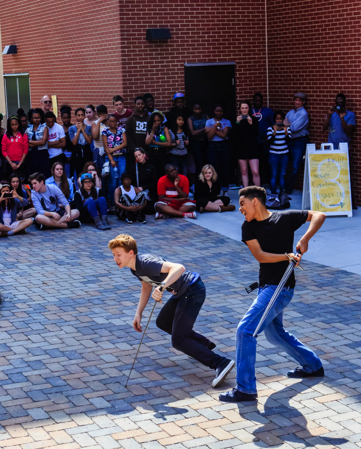 Two actors performing with swords in a public square