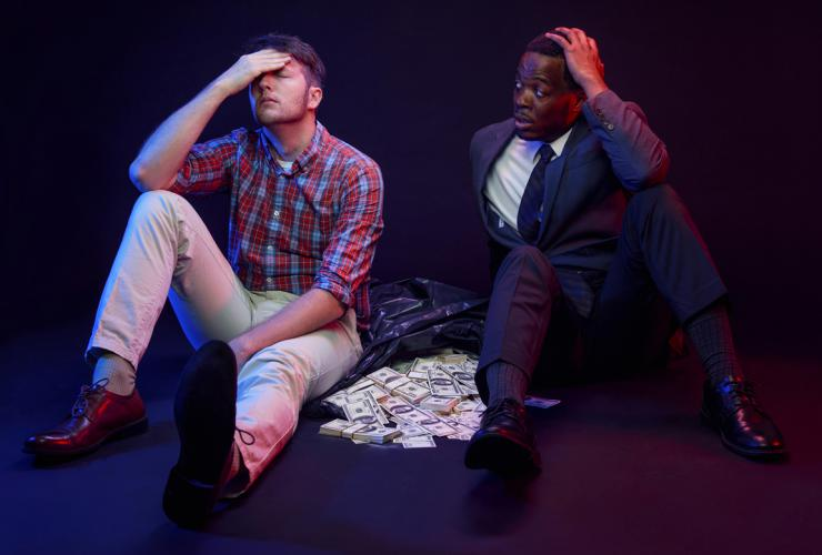 Two actors sitting with a bag of money