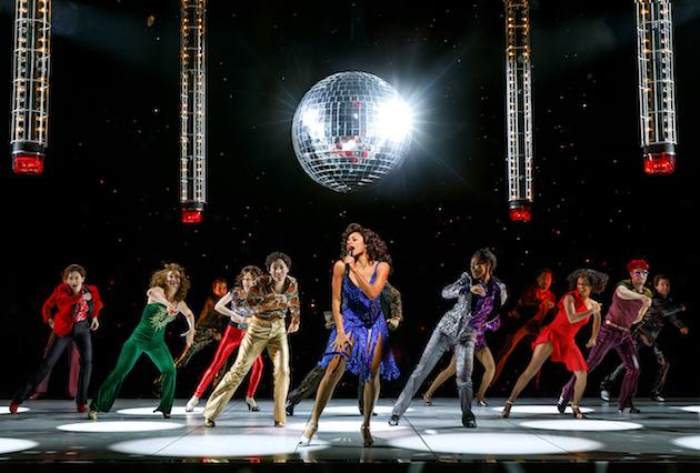a group of dancers onstage underneath a disco ball