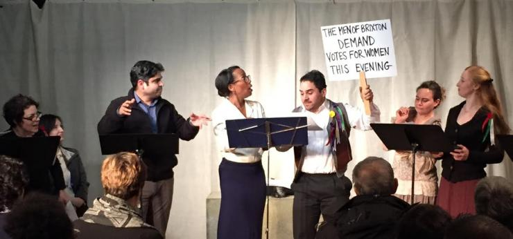 staged reading with actors holding a sign