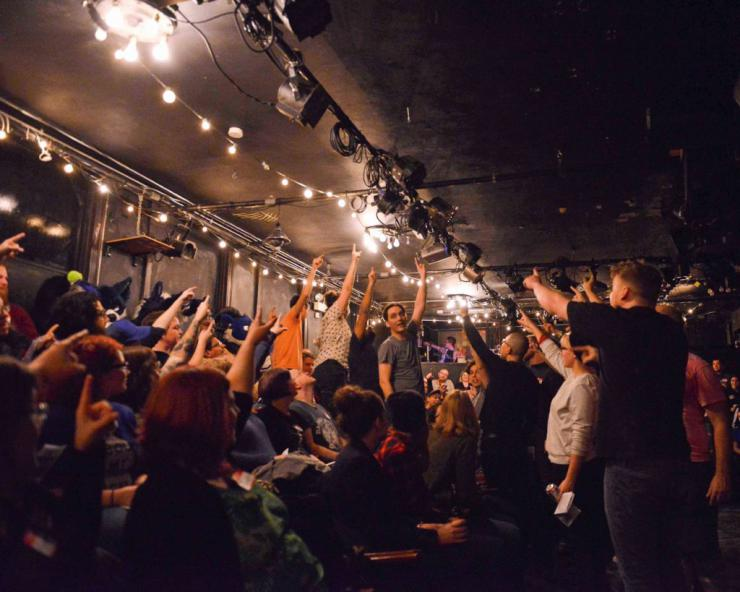 performers and audience pointing to the ceiling of a blackbox theatre
