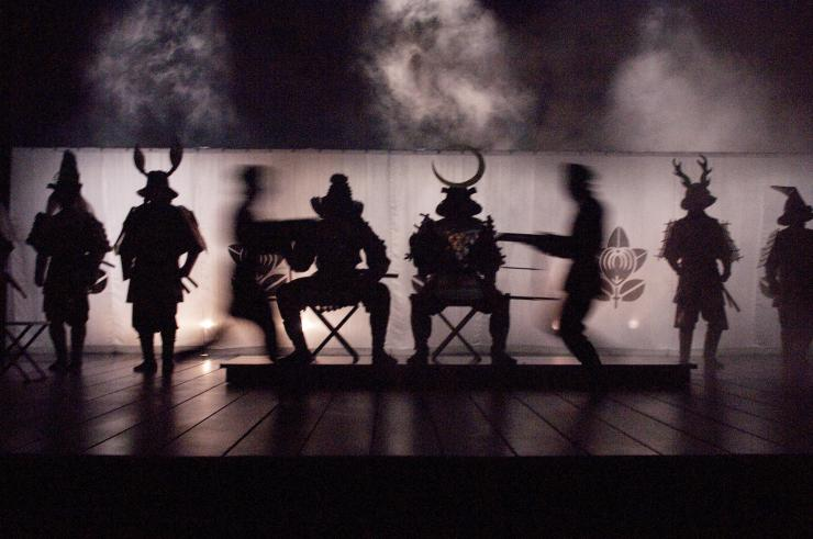 several silhouettes of actors in costume on stage