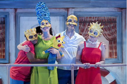 The cast on stage, in masks