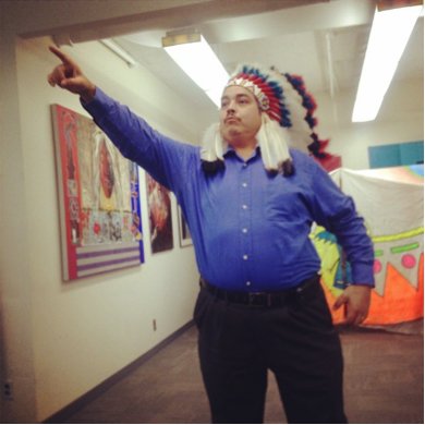 Man in native headdress pointing in a gallery