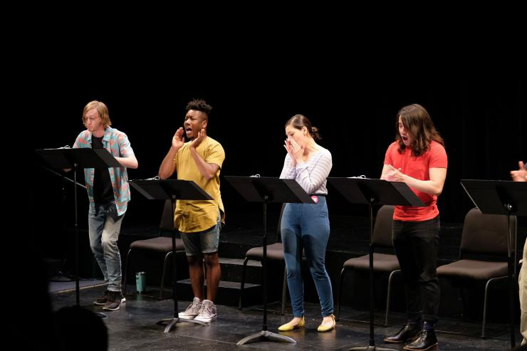 Four actors on stage at music stands.