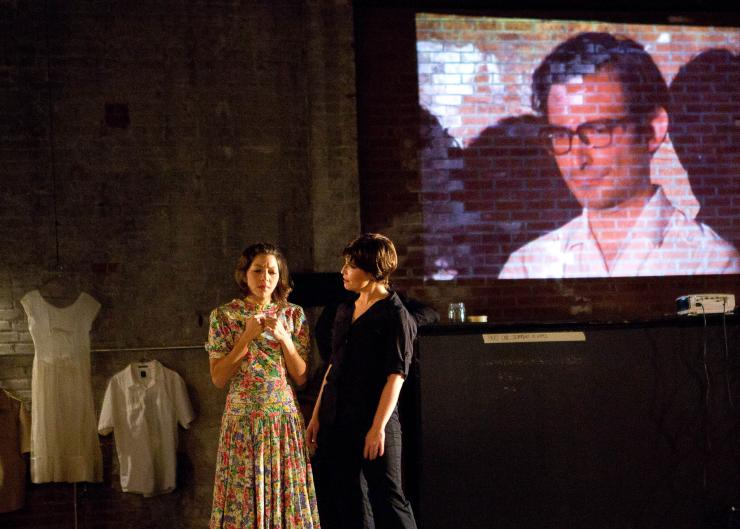 Two actors on stage with a projection