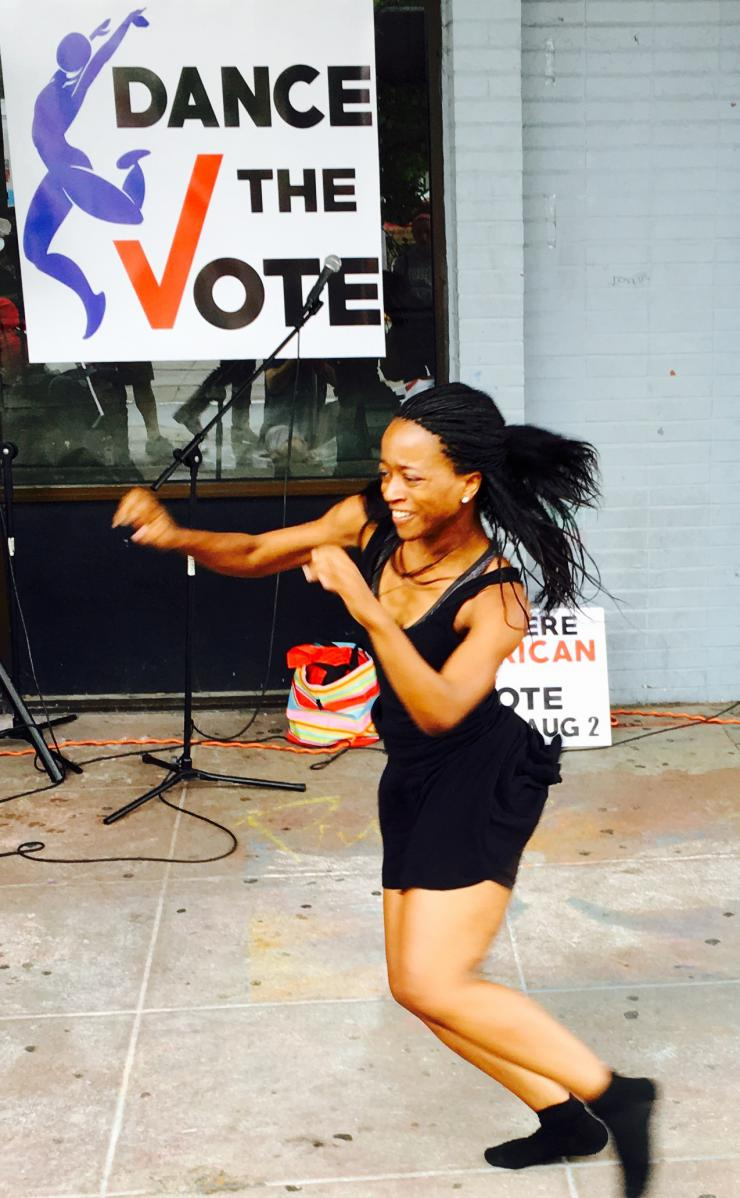 A woman dances in front of a sign that says Dance the Vote